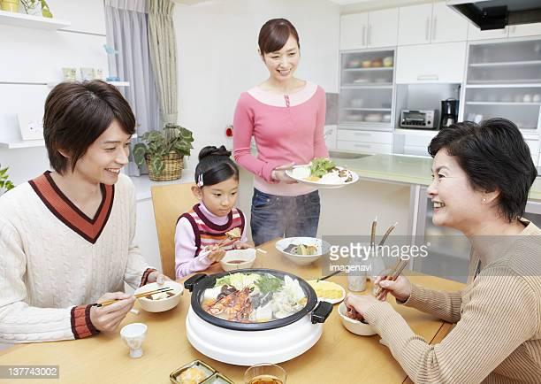Three-generation family sitting around yosenabe