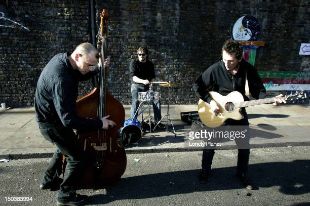 Three-piece band jamming on Brick Lane.