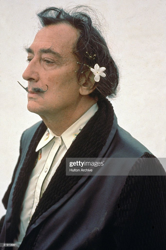 Threequarter profile portrait of Spanish surrealist painter Salvador Dali dressed in a smoking jacket with a flower in his hair early 1980s