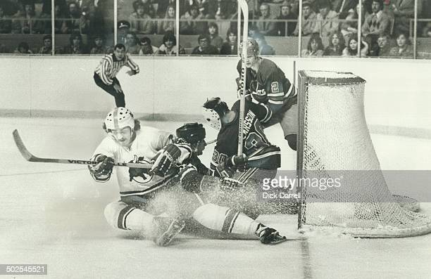 Three's A Crowd Rick Cunningham of Toros causs jamup in front of Winnipeg Jets' net as goalie Curt Larsson and teammate successfully block the way...