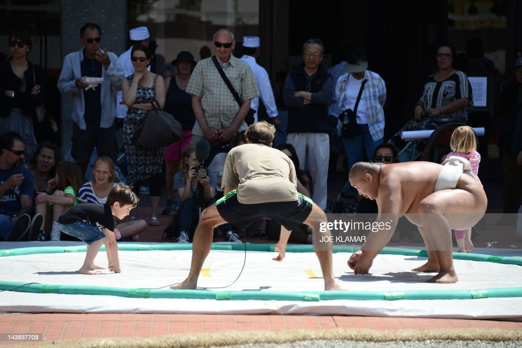 "Three-time World Sumo champion Byamba shares his knowledge with kids during the children's day LA Bloom at Little Tokio in Los Angeles, California on May 05, 2012. Bayamba was teaching kids the basic excercises and movements of Sumo and explaining their cultural significance. Mongolian-born Byambajav Ulambayar competed in sports since he was a child. By age 15, ""Byamba"" had captured national junior champion titles in judo, sambo, and Mongolian wrestling. At that time, he was invited to join professional Sumo team in Japan. At age 21, Byamba was invited to perform sumo in the film ""Oceans 13"". Since acting in 'Oceans 13', Byamba had performed in over 120 TV shows, films, commercials, and live events, all over the world. In just four years, he has traveled abroad over 50 times for his performances, and all over the United States. Some of his significant projects include being the mascot and face of Subaru Canada for the past three years, competing on 'America's Got Talent', spending a week on 'Gran Hermano' (Big Brother), with rave reviews, in Spain, performing sumo to packed arenas in India, and much more. AFP PHOTO /JOE KLAMAR"
