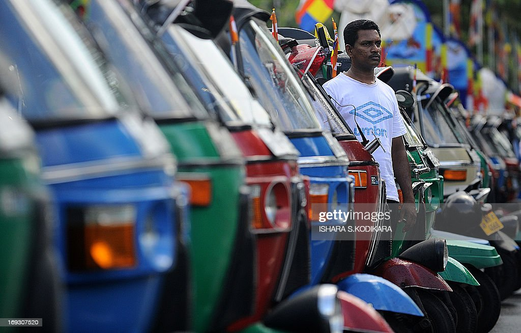 Three-wheeler taxis are seen lined up during an event where Buddhist flags were placed onto the vehicles in Colombo on May 23, 2013, ahead of the country's main Buddhist festival of Wesak. Sri Lankan Buddhists are preparing to celebrate Wesak, which commemorates the birth of Buddha, his attaining enlightenment and his passing away on the full moon day of May which falls on May 24 this year. AFP PHOTO/Ishara S. KODIKARA