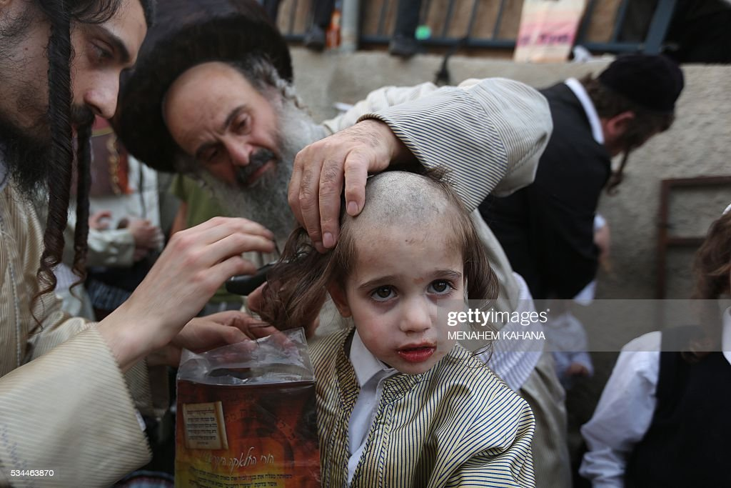A three-year old Jewish boy takes part in the traditional Halake ceremony, a first hair cut from his ultra-orthodox father, during a celebration at the grave site of Rabbi Shimon Bar Yochai in the northern Israeli village of Meron, on May 26 2016, at the start of the day-long holiday of Lag Baomer that commemorates the Jewish scholar's death. Thousands of religious Jews light large bonfires all night long and visit the shrine of Bar Yochai, one of the most prominent sages in Jewish history, during the holiday. / AFP / MENAHEM