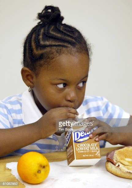 Threeyearold Andrea Woolfolk drinks milk as she eats her lunch at the Loop Lab School July 12 2004 in Chicago Illinois US Senator Dick Durbin later...