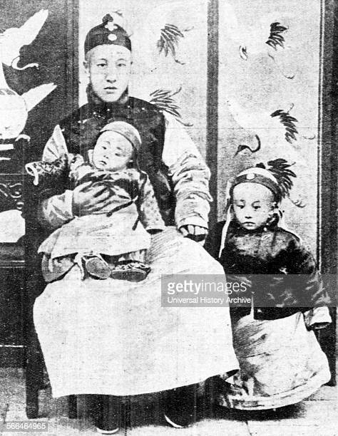 Threeyearold Chinese Emperor Puyi standing next to his father and his younger brother Pujie