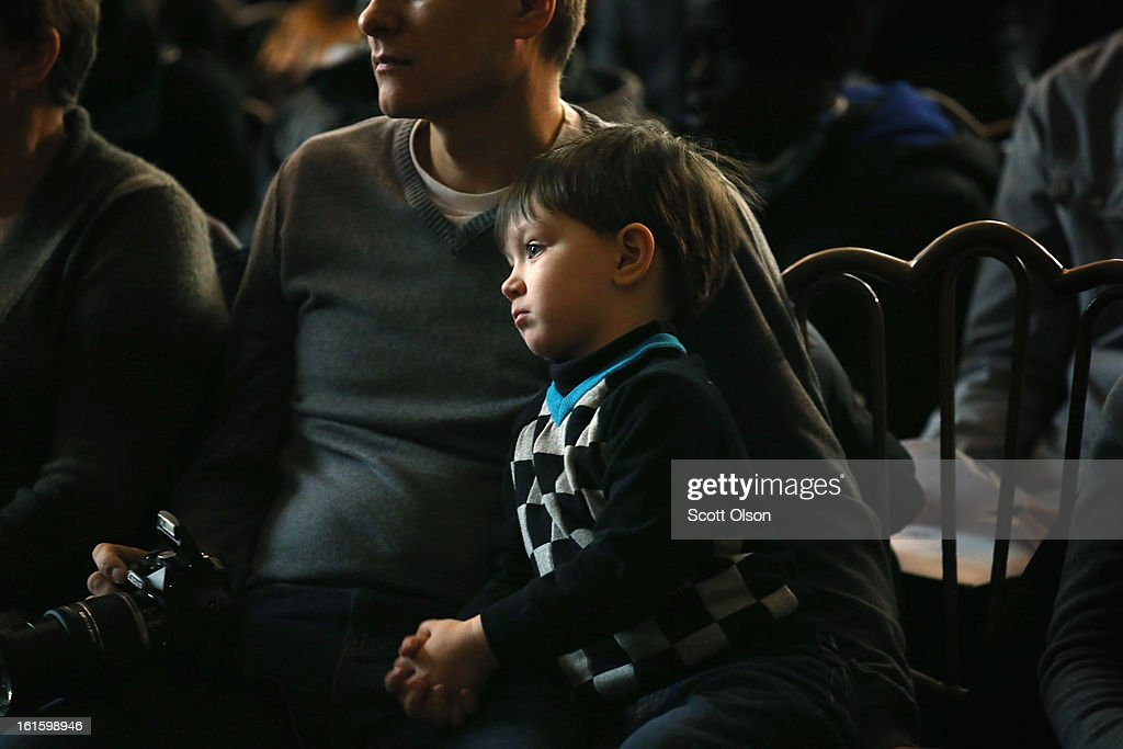 Three-year-old Emil Bugaian, who is from Moldova, watches with his father Igor while his nine-year-old brother Christian participates in a citizenship ceremony at the Chicago Cultural Center on February 12, 2013 in Chicago, Illinois. The ceremony was held to recognize as new U.S. citizens 62 children, ages 6-18, from 23 countries who were adopted from abroad or who derived U.S. citizenship when their immigrant parents were naturalized.