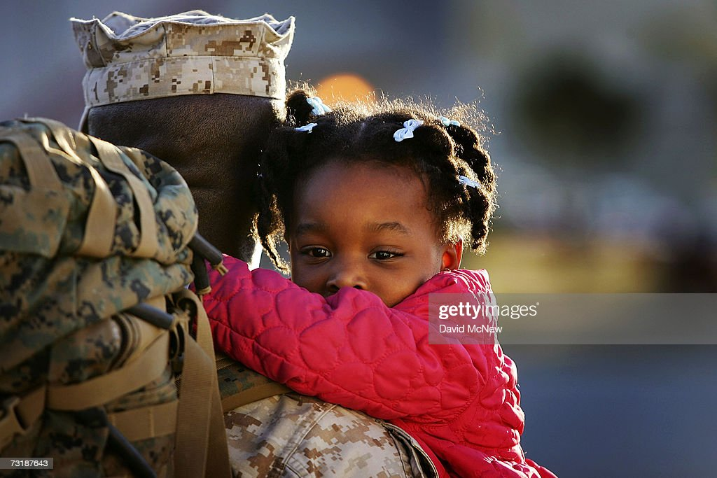 Threeyearold Gabrielle holds tight to her father Gunnery Sgt Godfrey Marille as Marines and sailors of the 1st Marine Logistics Group return home...