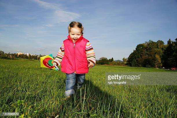 Three-year-old girl playing with a kite