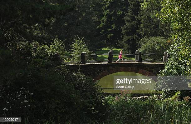 A threeyearold girl runs across a bridge in the Botanical Gardens during sunny weather on August 25 2011 in Berlin Germany Temperatures reached...