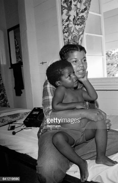 Threeyearold Jakarri Wilson the youngest survivor of the masssuicidemurder rites at Jonestown strokes his mother's chin as she talks to newsmen at...