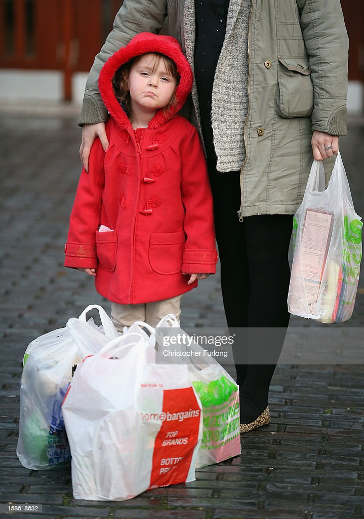 Three-year-old Lexie Hay poses beside her mum outside Liverpool Foodbank after collecting essential provisions for Christmas on December 21, 2012 in Liverpool, England. With Christmas only days away, volunteers at the Central Liverpool Foodbank at the Frontline Trust, have seen one of their busiest days of the year as they give out free food for the needy. The centre has been giving out festive treats as well as its normal food donation - feeding over 1000 individuals in its first year, including over 300 children.