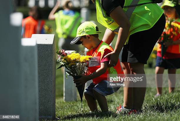 Threeyearold Matthew Ziehler of Centerville Ohio places flowers in front of a tombstone July 11 2016 at Arlington National Cemetery in Arlington...