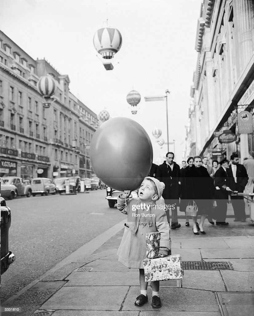 Threeyearold Peter Murphy holding a huge balloon is fascinated by the colourful decorations as he walks down Regent Street during a Christmas...