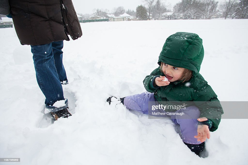 Three-year-old Virginia Krezmien of Greenfield, MA tastes some snow on December 27, 2012 in Greenfield, Massachusetts. A serious winter storm that caused tornados in the South on Christmas Day swept across the Northeast on Thursday, bringing snow, sleet, rain and causing dangerous travel conditions.