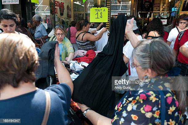 CONTENT] Thrifty shoppers congregate at a table at a sidewalk sale A $1 sign is in the background