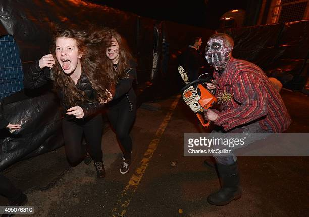 Thrill seekers react to a Chateau Le Fear cast member as he performs at the house of horror interactive walkthrough show on October 31 2015 in...