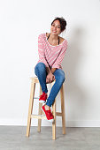 student vacation smile - thrilled beautiful ethnic girl sitting on a stool enjoying free time, white background studio