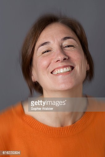 thrilled middle aged woman with brown hair laughing, blur effects : Bildbanksbilder