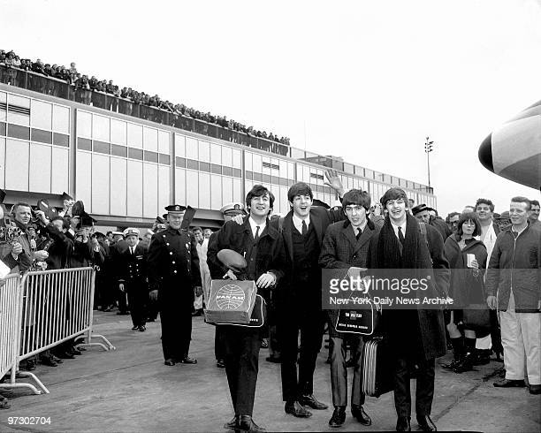 Throng is on hand to greet the Beatles as they stepped triumphantly from plane at Kennedy Airport for the first time from London for a 10day tour