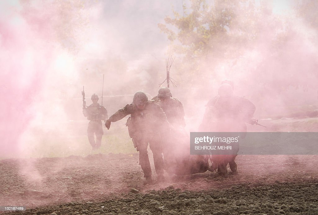 Through the smokes of a flare US Marines carry a wounded comrade who was hit by an Improvised Explosive Device to a Medevac helicopter of US Army's...