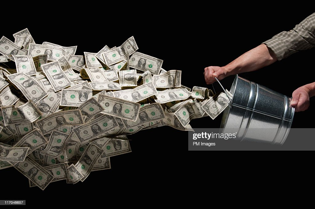 Throwing bucket of money : Stock Photo