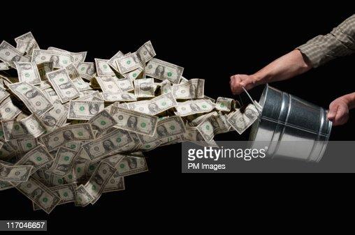 Throwing bucket of money : Stock-Foto