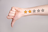 Mans hand showing thumb down and two star rating tattoo like drawing on gray background, internet rating concept