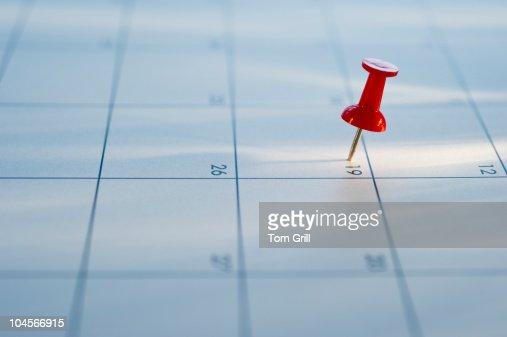 Thumb tack on calendar : Stock Photo