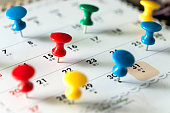 Various color thumb tack pins on calendar as reminder