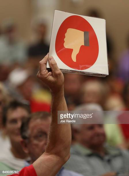 A thumbs down sign is held as people react as Rep Brian Mast speaks during a town hall meeting at the Havert L Fenn Center on February 24 2017 in...