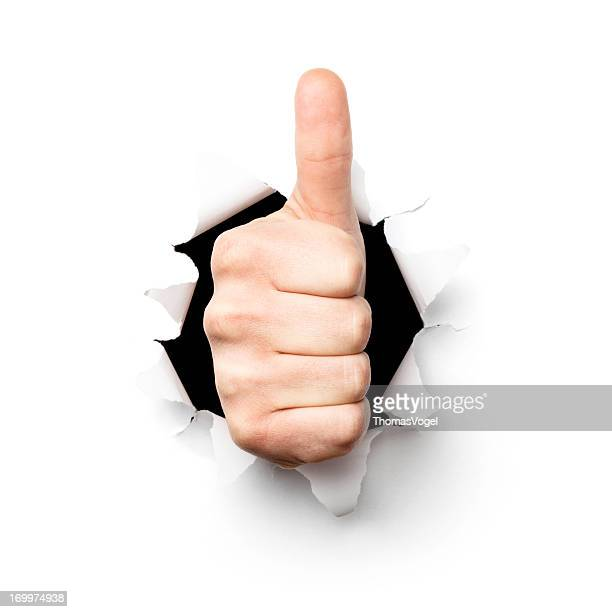 Thumbs up. Hand Tearing Hole Torn Paper Isolated Concept