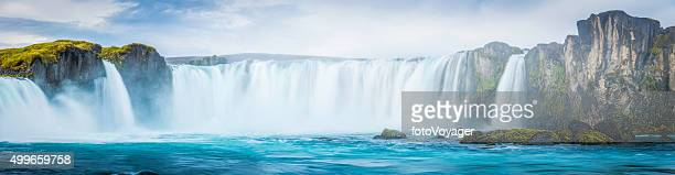 Thundering waterfalls cascading into blue mountain river panorama Godafoss Iceland
