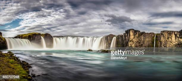 Thundering waterfalls cascading into blue mountain river panorama Godafoss Iceland