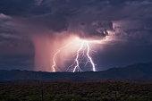 Thunderstorm lightning bolts strike the Four Peaks mountain range during the summer monsoon.