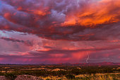 Vibrant lightning illuminates a bright orange and pink sky at sunset during a thunderstorm. Evening cloudscape with real lightning strike.