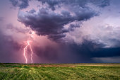 Thunderstorm with lightning bolts and dark, dramatic clouds over a field.