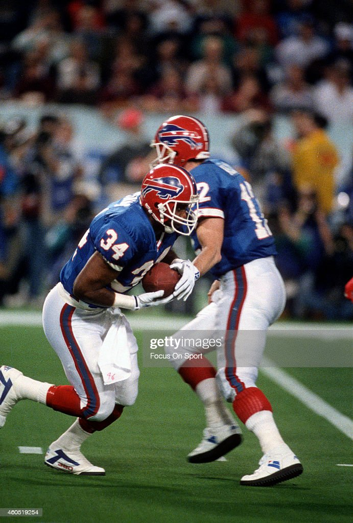<a gi-track='captionPersonalityLinkClicked' href=/galleries/search?phrase=Thurman+Thomas&family=editorial&specificpeople=575635 ng-click='$event.stopPropagation()'>Thurman Thomas</a> #32 of the Buffalo Bills takes the handoff from quarterback <a gi-track='captionPersonalityLinkClicked' href=/galleries/search?phrase=Jim+Kelly+-+American+Football+Player&family=editorial&specificpeople=216547 ng-click='$event.stopPropagation()'>Jim Kelly</a> #12 against the Washington Redskins during Super Bowl XXVI at the Metrodome in Minneapolis, Minnesota January 26, 1992. The Redskins won the Super Bowl 37-24.