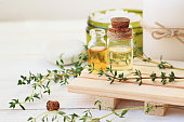Thyme essential oil. Bottles with extract, fresh green plant leaves.