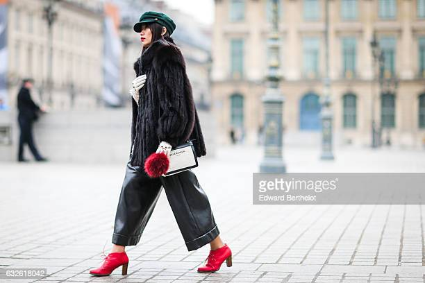 Thythu fashion blogger wears a green beret hat a fur coat black leather pants a red bag and red shoes outside the Alexis Mabille show at Place...