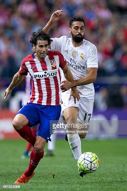 Tiago Mendes of Atletico de Madrid competes for the ball with Alvaro Arbeloa of Real Madrid CF during the La Liga match between Club Atletico de...