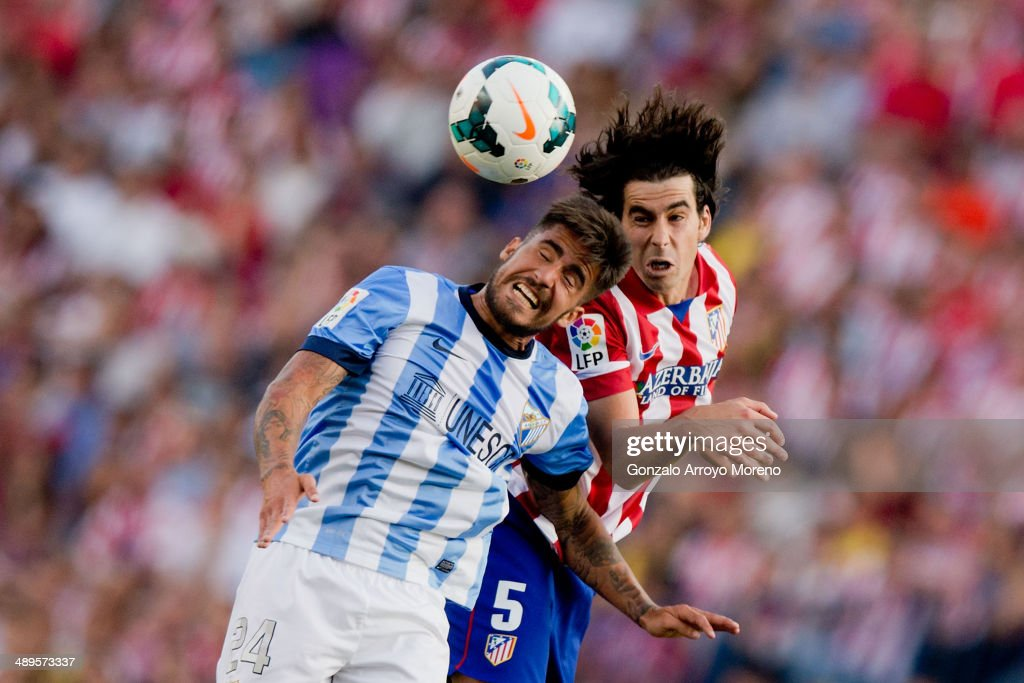 Tiago Mendes of Atletico de Madrid wins the header before Samuel Garcia Sanchez of Malaga CF during the La Liga match between Club Atletico de Madrid...