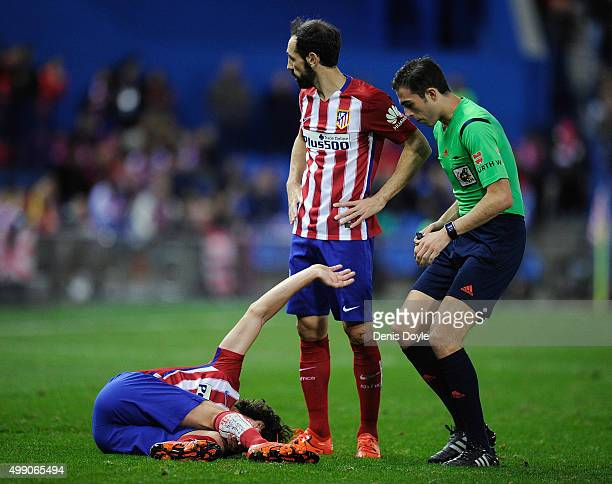 Tiago Mendes of Club Atletico de Madrid lies injured beside Juanfran during the La Liga match between Club Atletico de Madrid and Real CD Espanyol at...