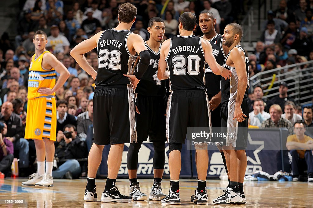 Tiago Splitter #22, Danny Green #4, Manu Ginobili #20, Boris Diaw #33 and Tony Parker #9 of the San Antonio Spurs huddle up during a break in the action as Danilo Gallinari #8 (L) of the Denver Nuggets looks on at the Pepsi Center on December 18, 2012 in Denver, Colorado. The Nuggets defeated the Spurs 112-106.