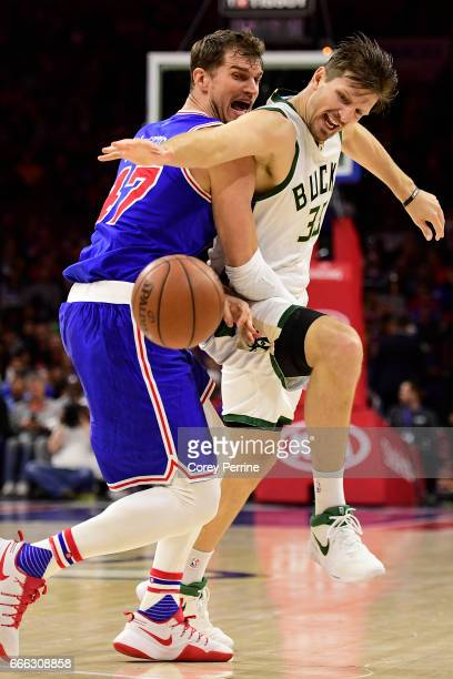 Tiago Splitter of the Philadelphia 76ers and Mirza Teletovic of the Milwaukee Bucks fight for a loose ball during the fourth quarter at the Wells...