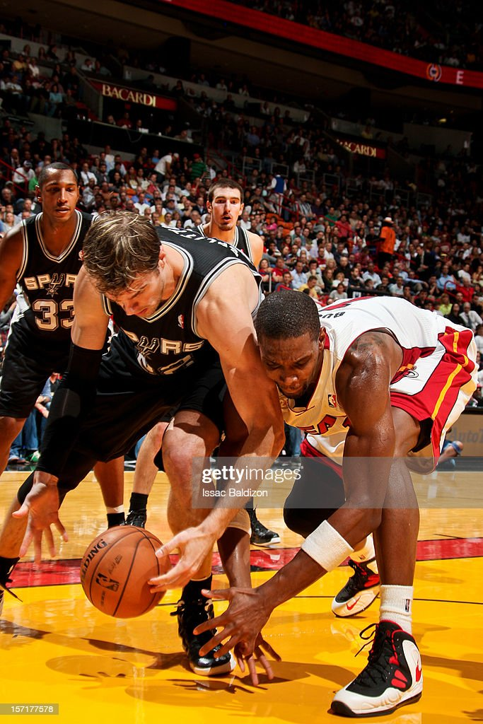 Tiago Splitter #22 of the San Antonio Spurs and Chris Bosh #1 of the Miami Heat try for a loose ball in the lane during their game on November 29, 2012 at American Airlines Arena in Miami, Florida.