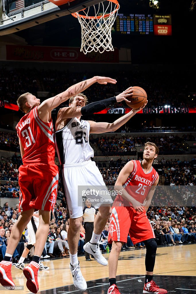 Tiago Splitter #22 of the San Antonio Spurs drives to the basket against Cole Aldrich #31 of the Houston Rockets on December 28, 2012 at the AT&T Center in San Antonio, Texas.