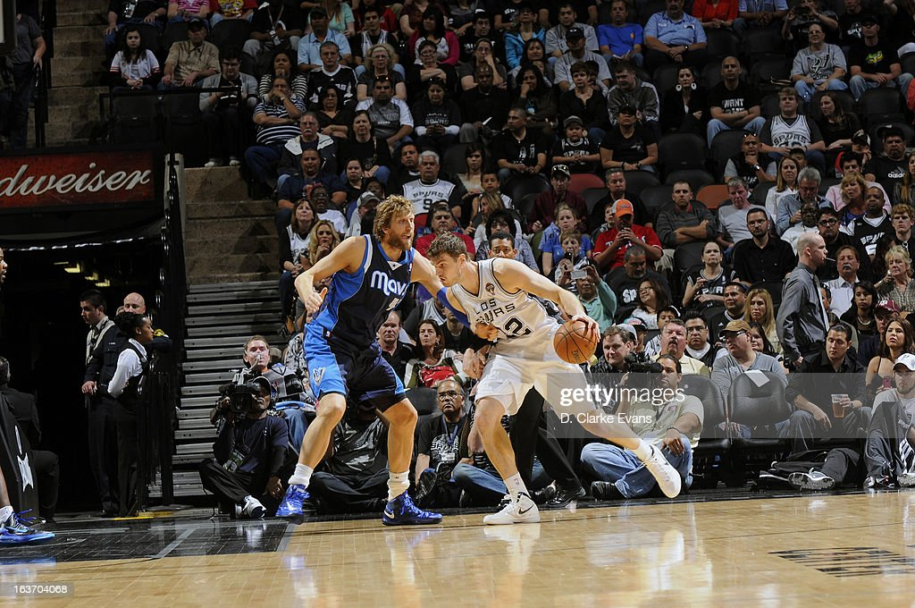 Tiago Splitter #21 of the San Antonio Spurs drives to the basket against Dirk Nowitzki #41 of the Dallas Mavericks on March 14, 2013 at the AT&T Center in San Antonio, Texas.