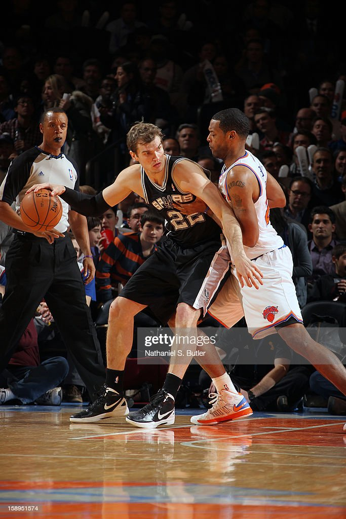 Tiago Splitter #22 of the San Antonio Spurs handles the ball against Marcus Camby #23 of the New York Knicks on January 3, 2013 at Madison Square Garden in New York City.