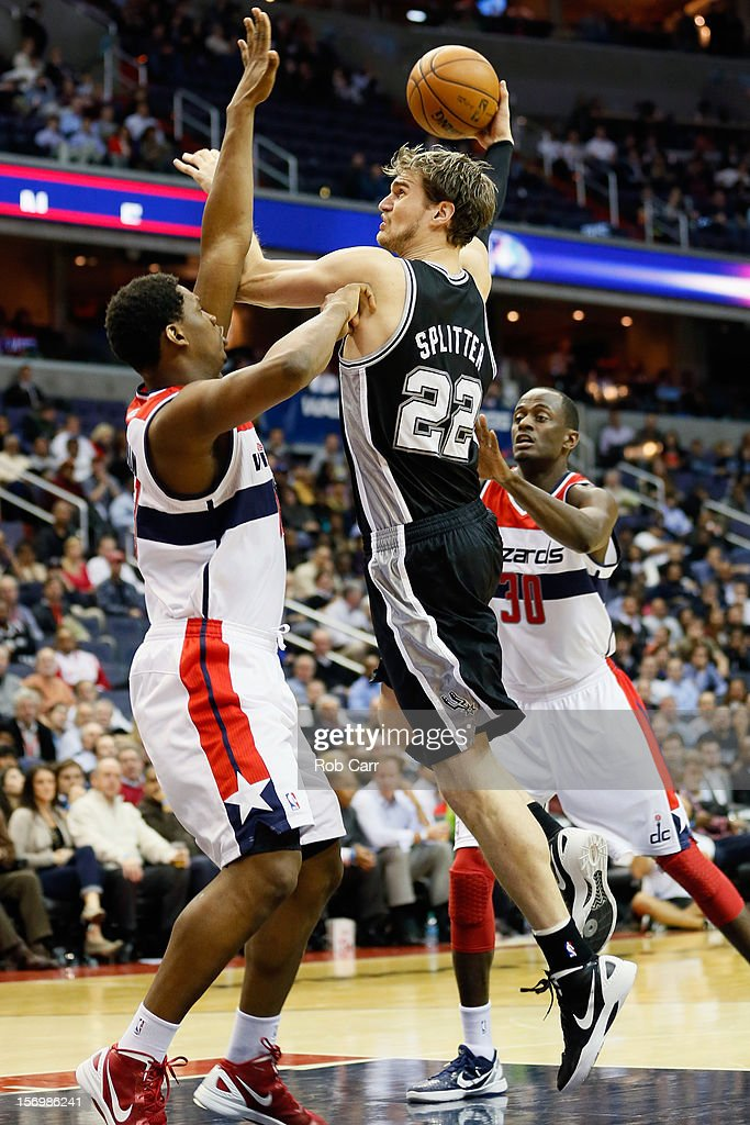 Tiago Splitter #22 of the San Antonio Spurs puts up a shot in front of Kevin Seraphin #13 (L) and Earl Barron #30 of the Washington Wizards during the second half at Verizon Center on November 26, 2012 in Washington, DC.