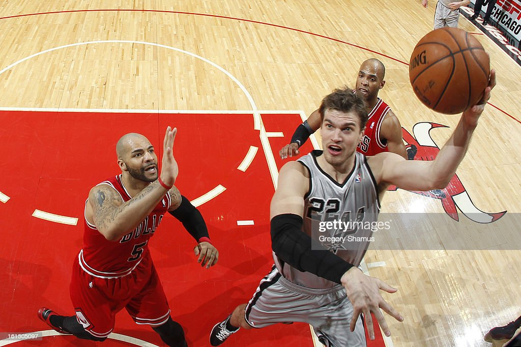 Tiago Splitter #22 of the San Antonio Spurs shoots a layup against Carlos Boozer #5 of the Chicago Bulls on February 11, 2013 at the United Center in Chicago, Illinois.